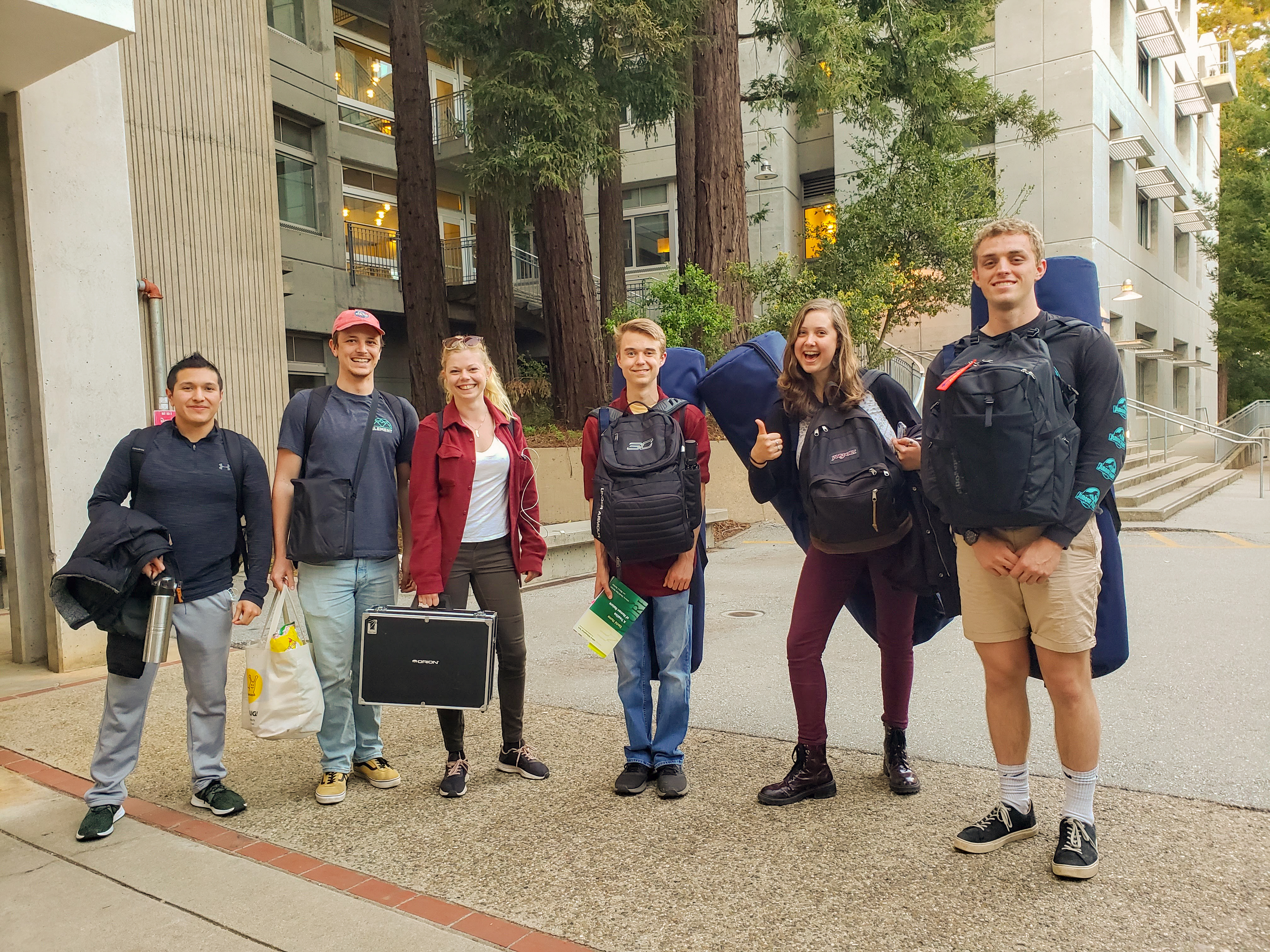 Students face the camera for a photo while carrying large tube like bags for telescopes and backpacks. They are students after all.