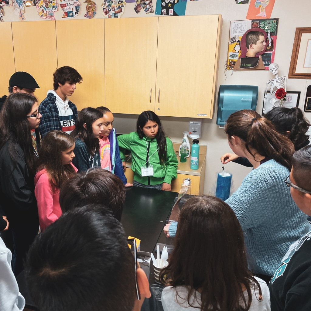 Superconductivity experiment demonstrated by two female physicists as students watch.